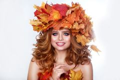 Beauty model girl with autumn bright leaves hairstyle. Beautiful Fashion female with Autumnal Make up and Hair style. Royalty Free Stock Images