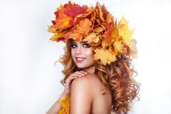 Beauty model girl with autumn bright leaves hairstyle. Beautiful Fashion female with Autumnal Make up and Hair style. Stock Photos