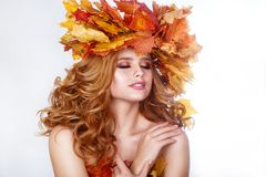 Beauty model girl with autumn bright leaves hairstyle. Beautiful Fashion female with Autumnal Make up and Hair style. Royalty Free Stock Photo