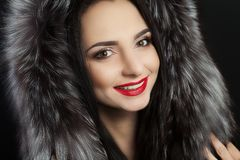 Beauty is a model girl in a black fur coat. Beautiful winter luxury woman. Photographed photo. Professional makeup. Red lips. Youn. G girl stock images