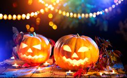 Beauty model girl in colorful bright lights with trendy makeupHalloween pumpkin head jack lantern with burning candles Stock Photo