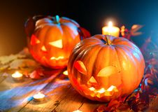 Beauty model girl in colorful bright lights with trendy makeupHalloween pumpkin head jack lantern with burning candles Stock Photos