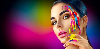 Beauty model girl with colorful paint on her face. Beautiful woman with flowing liquid paint. Beauty model girl with colorful paint on her face. Portrait of Royalty Free Stock Photos