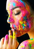 Beauty model girl with colorful paint on her face. Portrait of beautiful woman with flowing liquid paint Stock Image