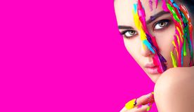 Beauty model girl with colorful paint on her face. Portrait of beautiful woman with flowing liquid paint. Isolated on pink royalty free stock photography