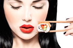 Beauty model girl eating sushi roll Stock Photos