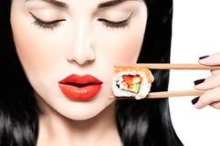 Beauty model girl eating sushi roll Stock Photos