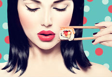 Beauty model girl eating sushi roll Stock Image