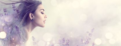 Beauty model girl with lavender flowers. Beautiful young brunette woman with flying long hair profile portrait stock image