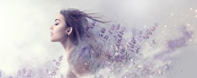 Beauty model girl with lavender flowers. Beautiful young brunette woman with flying long hair profile portrait