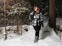 Beauty model girl in night winter forest. beautiful young Woman in fashionable Fur Coat and scarf Stock Image