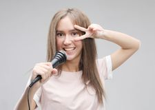 Beauty model girl singer with a microphone. Over grey background stock photography