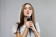 Beauty model girl singer with a microphone over light grey  background. Lifestyle and people concept: Beauty model girl singer with a microphone over light grey stock image