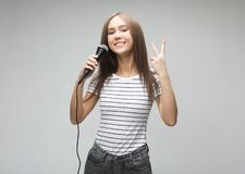 Beauty model girl singer with a microphone over light grey  background. Lifestyle and people concept: Beauty model girl singer with a microphone over light grey stock images