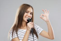 Beauty model girl singer with a microphone over light grey  background. Lifestyle and people concept: Beauty model girl singer with a microphone over light grey royalty free stock image