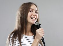 Beauty model girl singer with a microphone over light grey  background. Lifestyle and people concept: Beauty model girl singer with a microphone over light grey stock photography