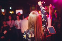 Beauty model girl singer with a microphone singing and dancing over holiday glowing background. Karaoke party singer stock image