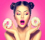 Beauty model girl taking colorful donuts. Dieting concept Royalty Free Stock Image
