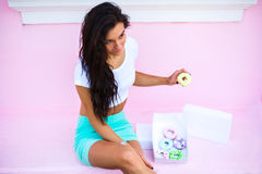 Beauty  model girl taking sweets and colorful donuts Stock Images