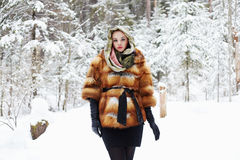 Beauty model girl in winter forest. beautiful young Woman in fashionable Fur Coat and scarf Stock Photo