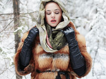 Beauty model girl in winter forest. beautiful young Woman in fashionable Fur Coat and scarf Stock Images