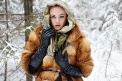 Beauty model girl in winter forest. beautiful young Woman in fashionable Fur Coat and scarf Royalty Free Stock Photo