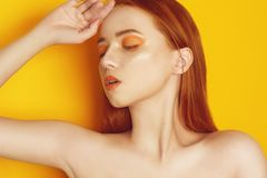 Beauty Model Girl with yellow / orange professional makeup. Orange eye shadow and lipstick  Fashion woman with long, straight hair stock photography