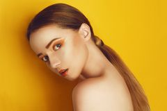 Beauty Model Girl with yellow / orange professional makeup. Orange eye shadow and lipstick  Fashion woman with long, straight hair royalty free stock photography