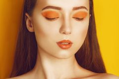 Beauty Model Girl with yellow / orange professional makeup. Orange eye shadow and lipstick  Fashion woman with long, straight hair royalty free stock photo