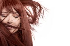 Beauty model with healthy long hair blowing over face. Beauty model with healthy long red hair blowing over her face wearing subtle eye makeup in a close up Stock Photography