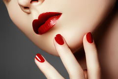 Beauty model. Manicured hand with red nails. Red lips and nails. Beautiful woman with luxury makeup and perfect manicure. Makeup concept royalty free stock photos