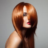 Beauty model with perfect long glossy red hair. Royalty Free Stock Images