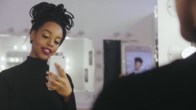 Beauty model photographing its reflection in makeup mirror on mobile phone stock video footage