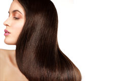 Beauty model showing perfect skin and long healthy brown hair. On white Stock Photo