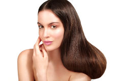 Beauty model showing perfect skin and long healthy brown hair. On white Stock Images