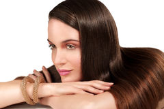 Beauty model showing perfect skin and long healthy brown hair. On white Royalty Free Stock Photos