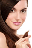 Beauty model showing perfect skin and long healthy brown hair. On white Stock Photography