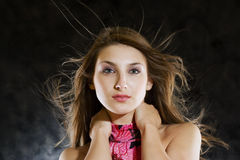 Beauty model in studio with hair blown by wind Stock Image