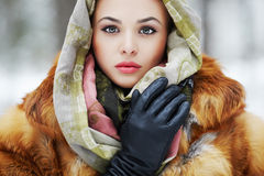 Beauty model in winter forest. beautiful young Woman in fashionable Fur Stock Images