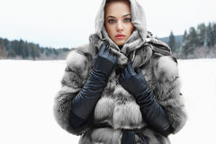 Beauty model in winter forest. beautiful young Woman in fashionable Fur Royalty Free Stock Image