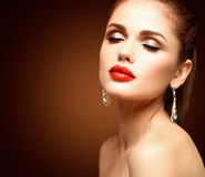 Beauty Model Woman with Long Brown Wavy Hair. Healthy Hair and Beautiful Professional Makeup. Red Lips and Smoky Eyes Royalty Free Stock Images