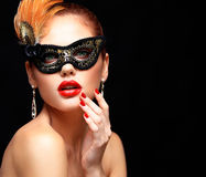 Beauty model woman wearing venetian masquerade carnival mask at party isolated on black background. Christmas and New Stock Images