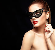 Beauty model woman wearing venetian masquerade carnival mask at party isolated on black background. Christmas and New Stock Photography