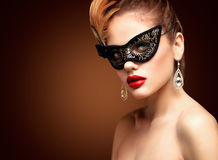 Beauty model woman wearing venetian masquerade carnival mask at party isolated on black background. Christmas and New Royalty Free Stock Image