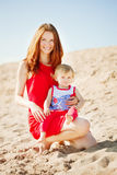 Beauty Mom and baby outdoors. Happy family playing on the beach. Royalty Free Stock Photography