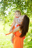 Beauty Mom and baby outdoors. Happy family playing in nature. Mo Stock Photo