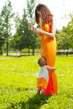 Beauty Mom and baby outdoors. Happy family playing in nature. Mo Royalty Free Stock Photography