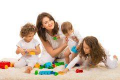 Beauty mom playing with her kids home. And sitting together on fur carpet Stock Image