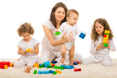 Beauty mom playing with her three kids. Home and sitting together on fur carpet Royalty Free Stock Photos