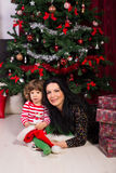 Beauty mom and son sitting near Xmas tree Stock Image